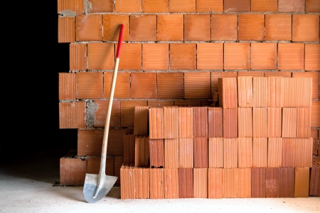 Brick wall with shovel, bucket and many bricks in a under construction masonry site  photo