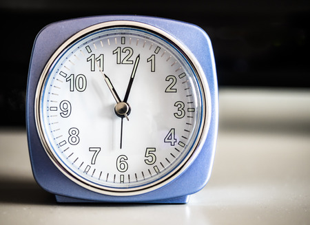Old fashioned azure morning alarm clock, display eleven, over a bedroom forniture