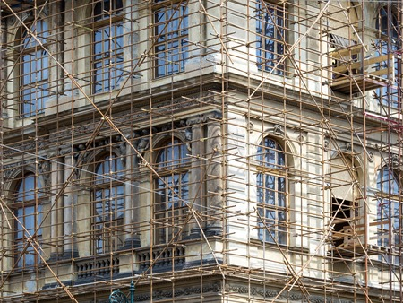 renovate old building facade: Fragment of scaffolding against house wall in Prague Stock Photo