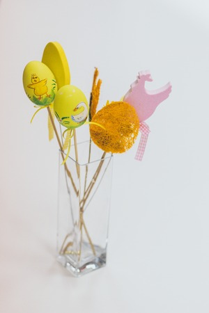 Easter decoration with a bunny rabbit, eggs and flowers in a glass vase on a white background