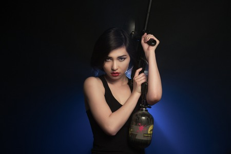 Young athletic woman with gun asian girl