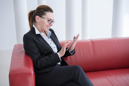 25s: Mature Businesswoman with Digital Tablet in Office Stock Photo