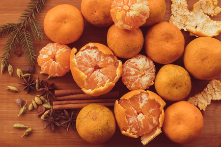 orange peel clove: tangerines, orange slices, stars cardamom and cinnamon sticks on a wooden table