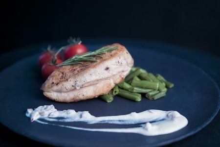 roquette: chicken steak with salad, raw tomatoes on plate Stock Photo