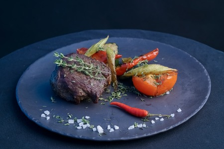 Grilled beef steak with baked vegetables on plate Stock Photo