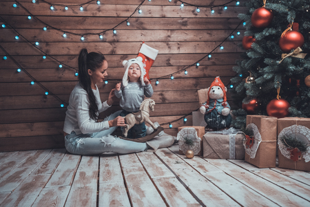 decorate: Young mother and her child at xmas Eve under a fir-tree