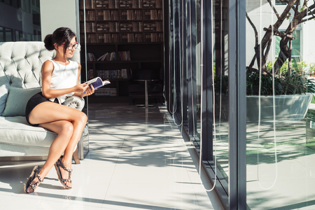 Young sexy woman reading in a modern business lounge
