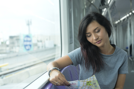 internet terminal: young adult girl with a map in sky train in Thailand