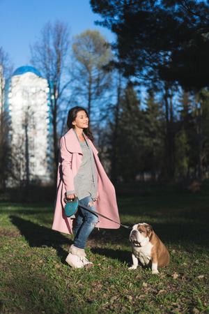 Pretty woman with her dog in the park
