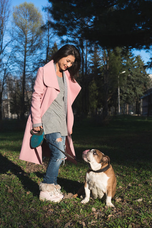 Beautiful young woman with her bulldog in the park