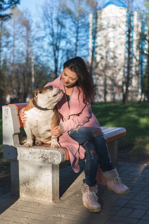 Beautiful woman with her dog sitting on bench