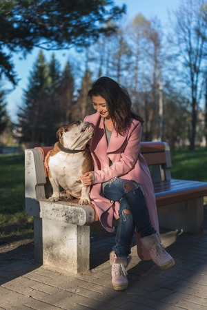 Beautiful young girl with her dog in the park