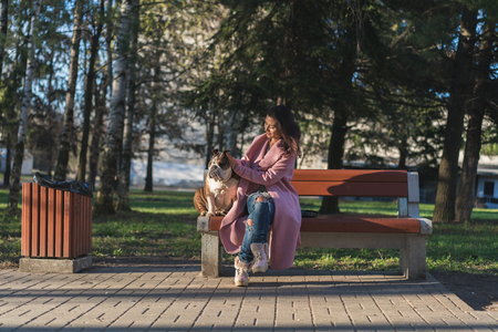 Beautiful woman sitting with her dog in the park 스톡 콘텐츠