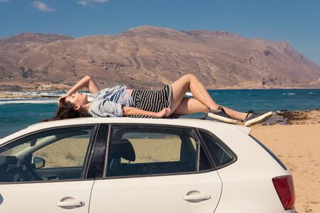 Woman lying on a white car Banque d'images