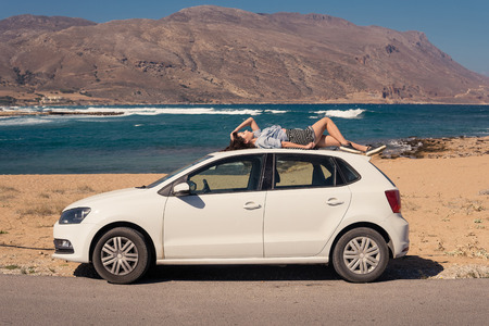 Woman relaxing on a white car top