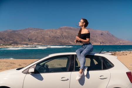 Woman on a white car at seaside