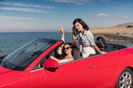 young happy women in cabriolet at seaside