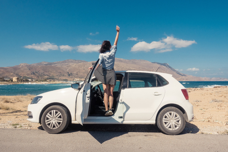 Happy young girl standing on the white car Stockfoto
