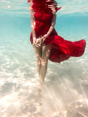 Underwater in the sea with the purest water. Beautiful girl in a scarlet dress and flowing hair. 스톡 콘텐츠