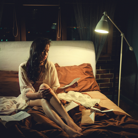 Unhappy woman in bed with love letters Banque d'images