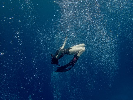 A young woman free diving in the bubbles 스톡 콘텐츠