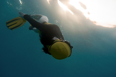 A young woman free diving in the pacific ocean