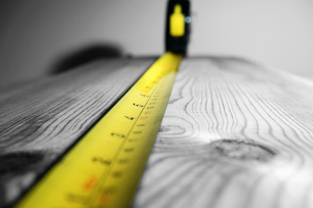 millimetre: Selective color image of a tape measure on a piece of wood