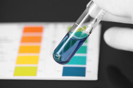 Persona que llevaba guantes de la prueba del pH de un producto químico en un tubo de ensayo Foto de archivo - 67204184