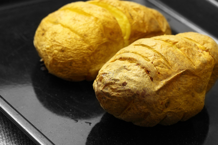 Baked potatoes cooked on a baking tray. Stock Photo