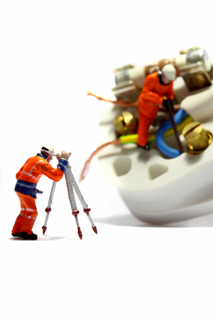 Miniatuur schaalmodelwerkers die een stekker van het Verenigd Koninkrijk bedraden