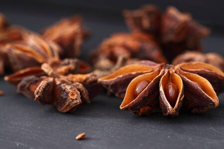 asian flavors: Star Anise on a black wood background Stock Photo