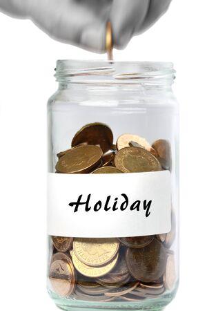 fund: Man adding coin to holiday fund jar