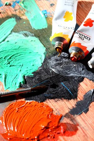 brush painting: Oil paint tubes and brush on a mixing board Stock Photo
