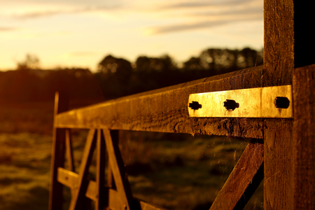 Hölzernes Bauernhoftor bei Sonnenaufgang Standard-Bild
