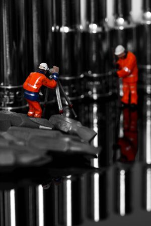 Miniature scale model construction workers with a socket set and screwdriver bits