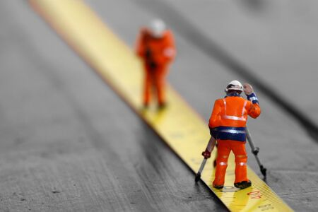 Scale model construction workers on a tape measure with selective colour