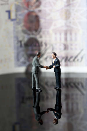Miniature scale model business figures standing in front of a twenty pound note sterling. Stock Photo