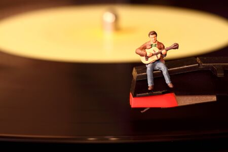 stylus: Scale model miniature musician performing on a vinyl record. Stock Photo