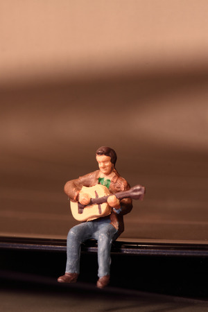 Scale model miniature musician performing on a vinyl record. Stock Photo