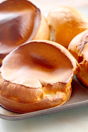 Freshly cooked Yorkshire puddings in a baking tray.