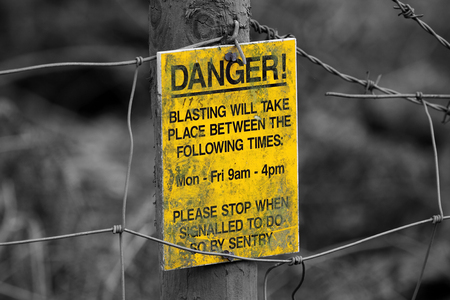 corrosion: Selective colour image of a danger explosives sign Stock Photo