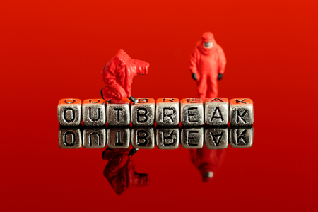 Miniature scale model team in chemical suits with the word outbreak on beads