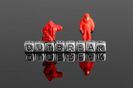 hazardous material team: Miniature scale model team in chemical suits with the word outbreak on beads