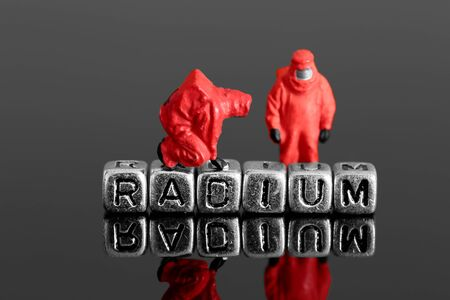 radiation protection suit: Miniature scale model team in chemical suits with the word radium on beads