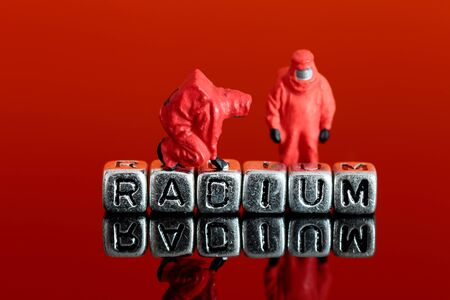 Miniature scale model team in chemical suits with the word radium on beads