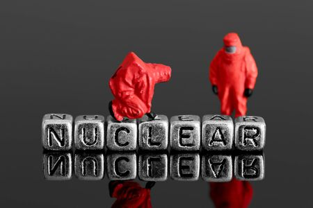 radiation protection suit: Miniature scale model team in chemical suits with the word nuclear on beads Stock Photo