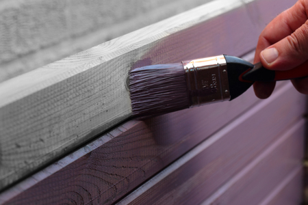 Selective colour image of wood being stained with a paintbrush