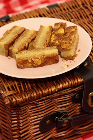 Almond cake slices on a plate with a picnic basket