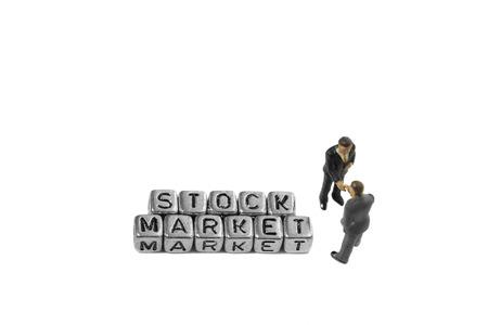 Miniatuurschaalmodelzakenlieden met de geïsoleerde woordenmarkt op parels Stockfoto