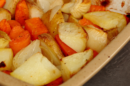 Roasted potatoes, carrots and onions in a ceramic dish 免版税图像